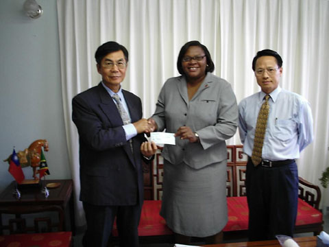 Resident Ambassador of the Republic of China on Taiwan, His Excellency John K. Liu (l) presents monetary contribution to Acting CEO of the St. Kitts Tourism Authority, Ms. Christine Walwyn, while Counselor, Mr. Franklin Chen looks on.