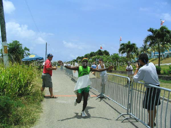 Grenadian olympic relay team member crossing the fininsh line in 2004 St Kitts Triathlon