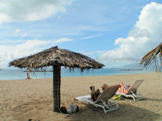Photo of tourists relaxing on Pinnneys Beach in Nevis. Perfect spot for a family beach vacation.