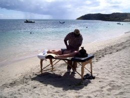 St Kitts tours and Island Safaris with Captain Sunshine Tours. St Kitts photo of Captain Sunshine Tours St Kitts massage on the beach with St Kitts masseur Kenny 'Captain Sunshine' Richardson.